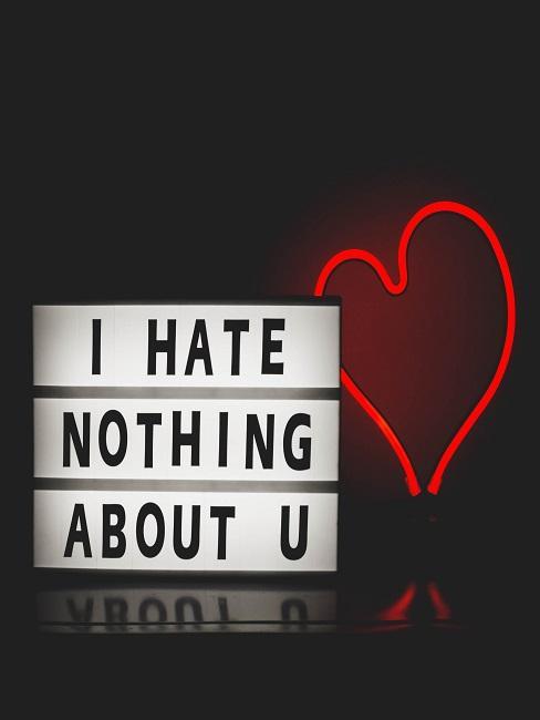 """Lightbox """"I hate nothing about u"""" neben einem leuchtenden Herz in Rot vor schwarzem Hintergrund"""