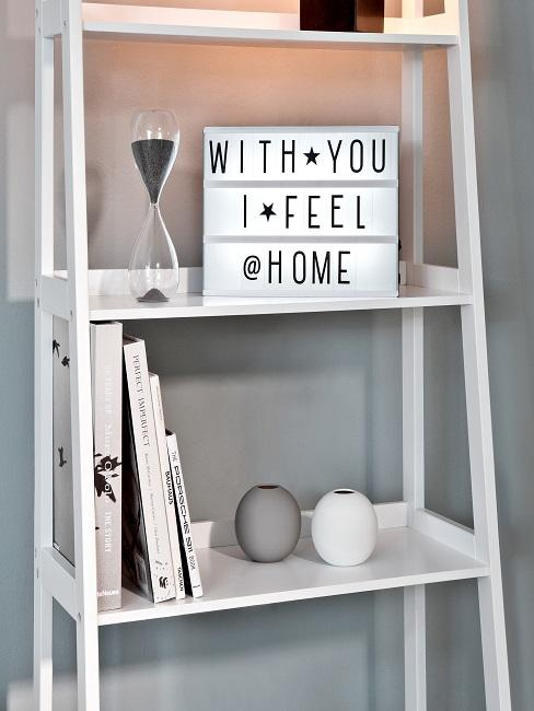 "Regal in Weiß mit Lightbox ""With you i feel @ home"" neben einer Sanduhr"