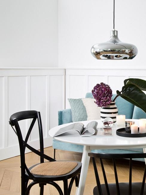 Ein runder Tisch in Weiß, daneben ein schwarzer Stuhl mit Wiener Geflecht, im Hintergrund ein blaues Sofa