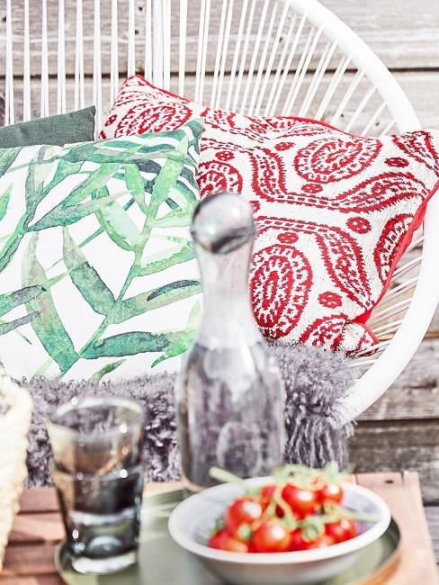 Stuhl in Weiß auf einem Balkon hinter einem Tisch, darauf zwei schöne Dekokissen