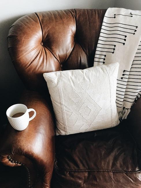 Brązowa skórzana sofa z jasną poduszką, kocem i filiżanką kawy na podłokietniku.