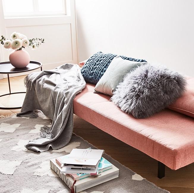cama rosa con manta gris y cojines decorativos
