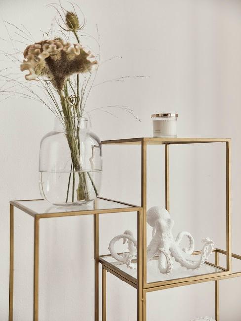 Szklany wazon z egzotycznymi roślinami, obok świeca i figurka ośmiornicy.