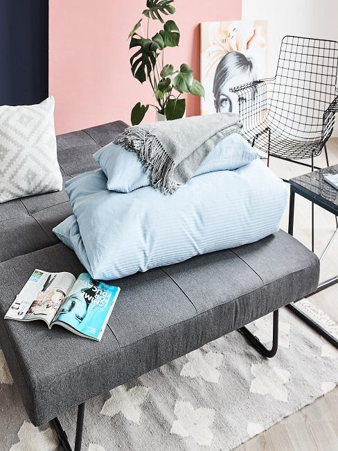 Graues Schlafsofa mit zusammengelegter Bettwäsche auf eiem Teppich neben Stühlen und dem Couchtisch
