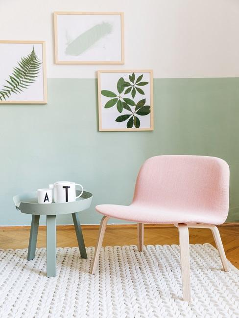 Chaise en rose à côté d'une petite table basse devant un mur peint horizontalement en deux couleurs : vert en bas et crème en haut