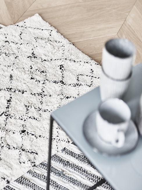 Een lichtgekleurd tapijt, met een tafel en koffiekopjes erop.