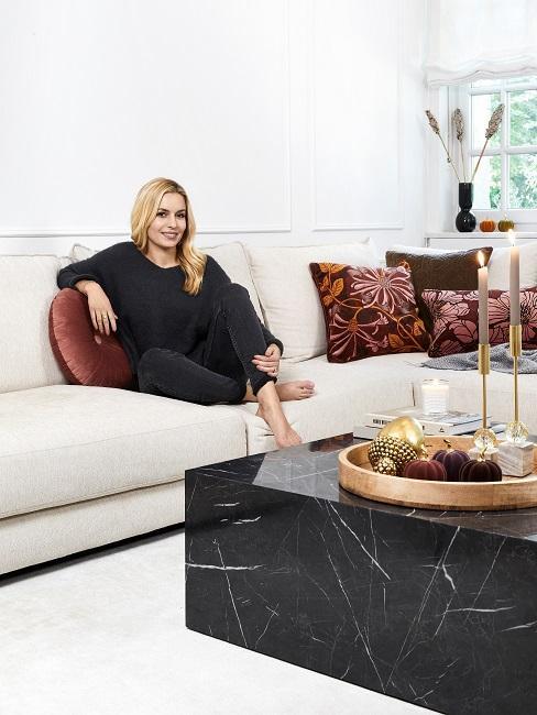 Westwing Gründerin Delia Fischer sitzt auf ihrem Sofa neben einem Couchtisch in Schwarz auf dem ein tablett mit Kürbis Deko steht