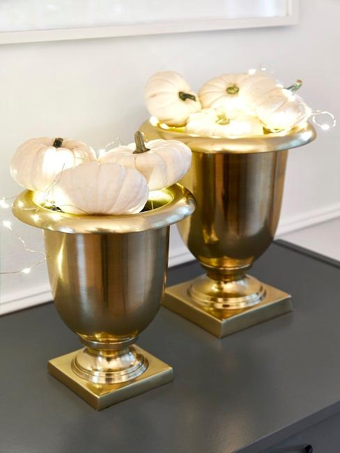 Close-up of two golden trophies filled with white pumpkins and fairy lights.