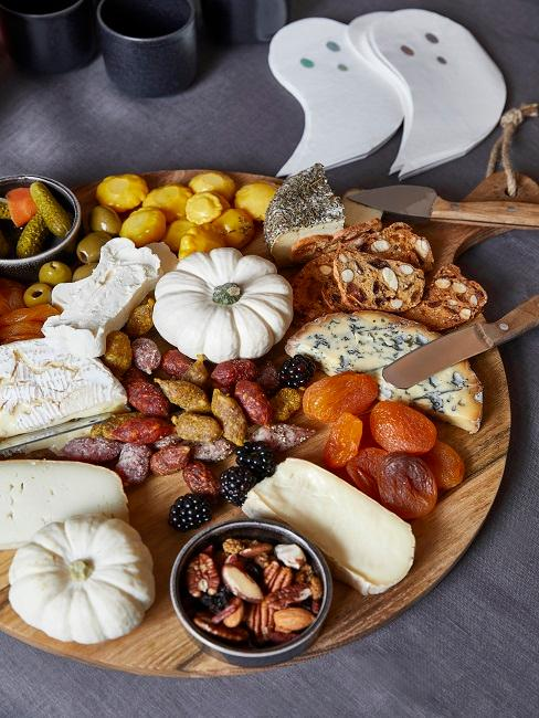 Tray with snacks and white pumpkins for decoration