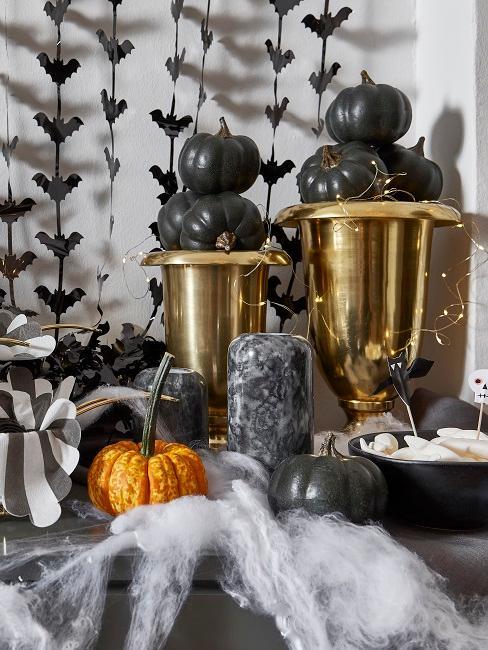 Zwei goldene Pokale auf einer Anrichte mit schwarzen Deko Kürbissen gefüllt.