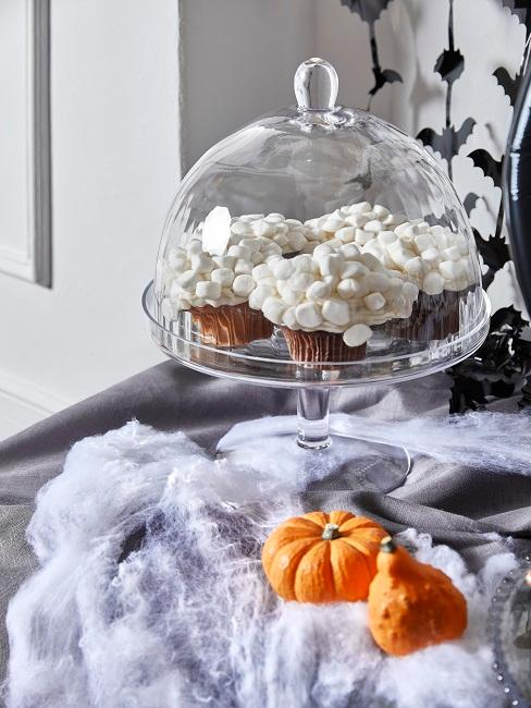 Cake stand with muffins and orange pumpkins for decoration.
