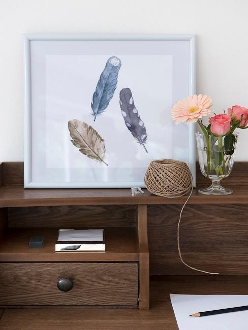 Bureau en bois foncé avec une impression encadrée de plumes, à côté d'un vase de fleurs