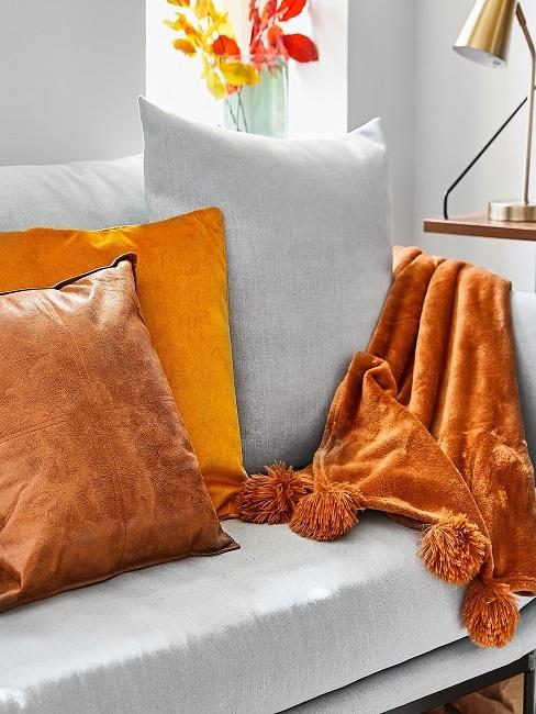 Sofa in Grau mit Kissen und Decke in Kurkuma