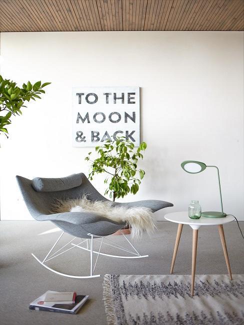 Soggiorno con una sedia, un tavolino su un tappeto, sullo sfondo un murale e piante