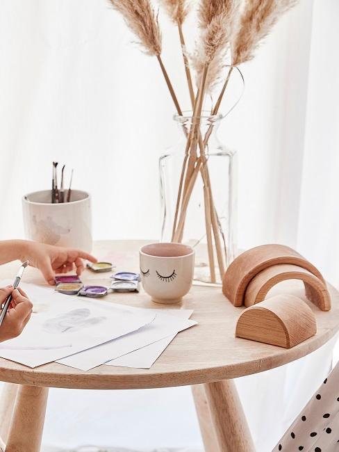 Kleine ronde houten tafel om op te schilderen, pampagras in een doorzichtige vaas als decoratie
