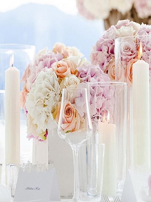 Décoration de table de mariage avec une composition des fleurs couleur blanc et pastel, des bougies blanches et un verre à vin