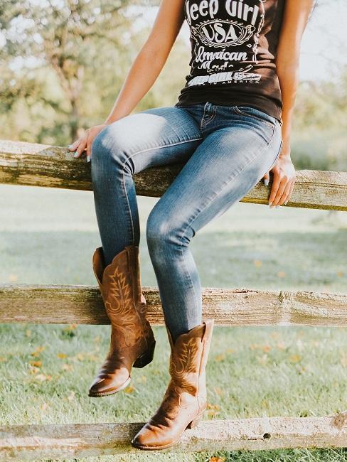 Frau im Western-Look mit Jeans und Cowboy-Stiefeln auf einem Holzzaun sitzen