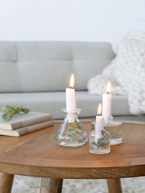Sofa in hellem Grau hinter einem runden Holz-Couchtisch mit drei Kerzen im Glas