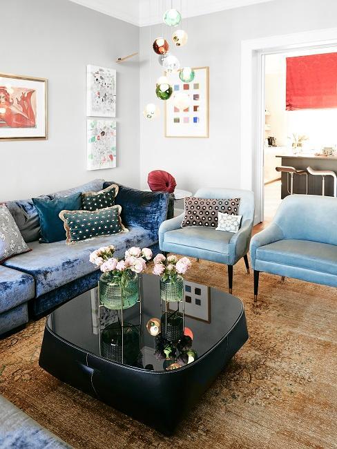 Design-Wohnzimmer von Dr. Barbara Sturm mit einem bauen Samtsofa und zwei blauen Samtsesseln und einem schwarzen, glänzenden Couchtisch