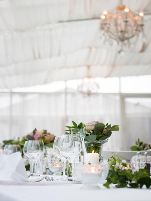 Hochzeitszelt mit gedeckter Tafel mit klassischer Deko, darüber ein edler Kronleuchter
