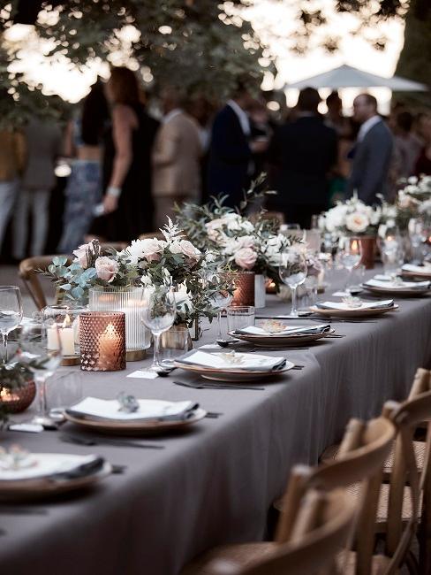 Gedeckte Outdoor Tischtafel im Boho Stil mit Blumen und Kerzen