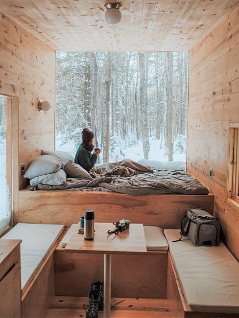 Eine Frau sitzt auf dem Bett in einem Tiny House und blickt aus dem Fenster.
