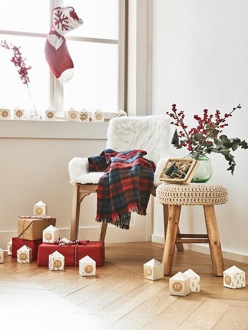Fensterecke in einem hellen Wohnzimmer mit eiem gemütlichen Stuhl ud einem Hocker mit Deko, daneben und auf dem Fensterbrett Teile eines Adventskalenders und verpackte Geschenke