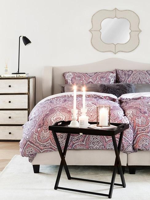 Helles Schlafzimmer mit Paisley-Bettwäsche in Beerentönen, gemütlich durch einen kleinen Beistelltisch mit Kerzen-Deko