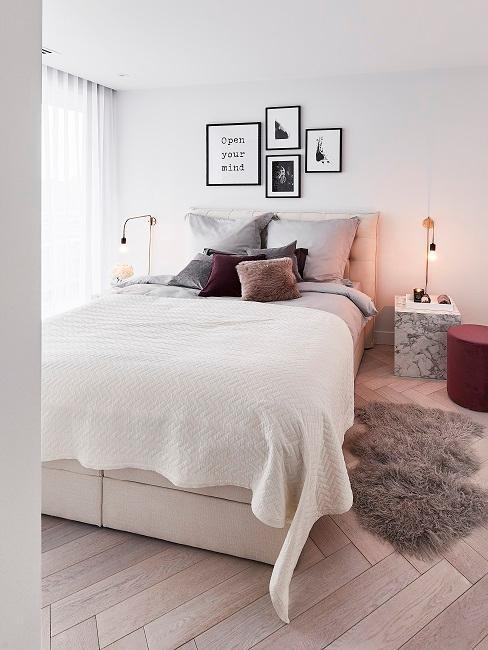 Helles Bett in einem Schlafzimmer mit gemütlichen Kissen, einem Fellteppich und Wandbildern