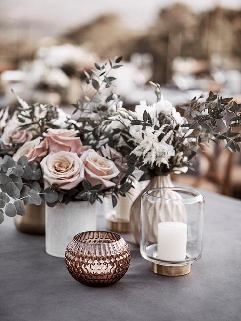 Eukalyptus Zweige in kleinen Blumenvasen mit rosa und weißen Rosen.