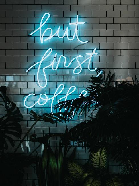 """Neon-Leuchtschrift an einer weißen Fließenwand mit den Worten """"But first Coffee""""."""