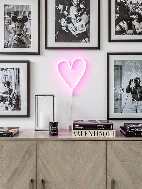 Neon-Leuchtschrift in Form eines Deko-Herzes über einem Sideboard im Wohnraum.