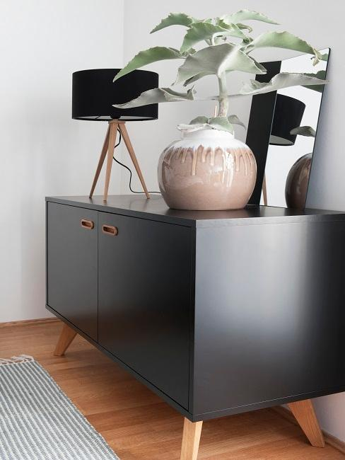 Decorate black chest of drawers with black lamp, mirror and plant