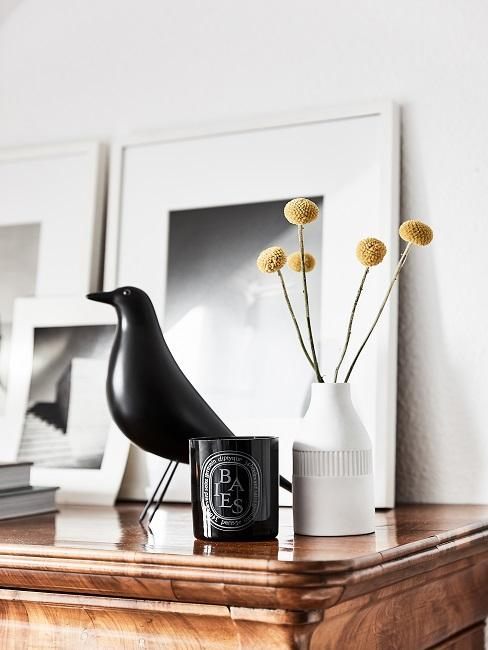 Decorate chest of drawers with black decorative bird, pictures, flower vase and scented candle