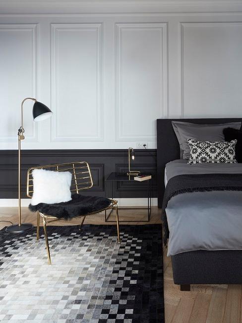 Schlafzimmer in Schwarz Weiß mit grafisch gemustertem Teppich und goldfarbenen Details