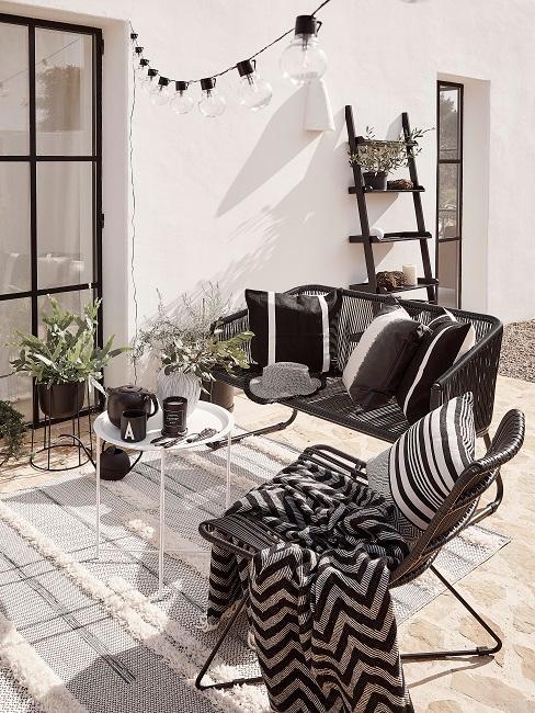Terrasse mit Möbeln und Deko Kissen und Decken in Schwarz-Weiß, darüber eine schlichte Lichterkette