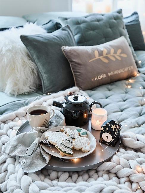 Bett mit vielen Kissen und einer gemütlichen Chunky Knit Decke, darauf ein Tablett mit Teller, Tasse, einer Teekanne und Kerzen, um und auf dem Tablett eine sehr zierliche Lichterkette als gemütliche Deko