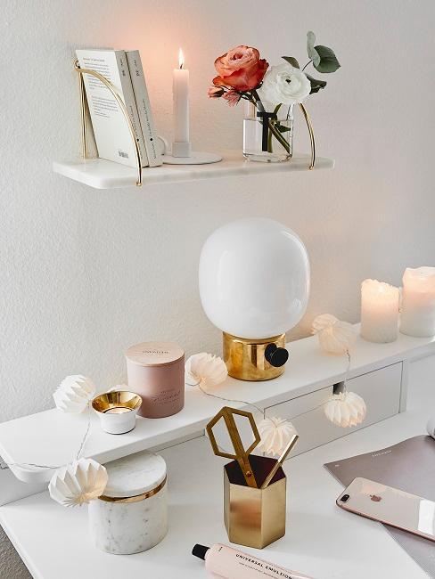 Schreibtisch in Weiß mit Deko und einer weißen Lichterkette, darüber ein Wandregal