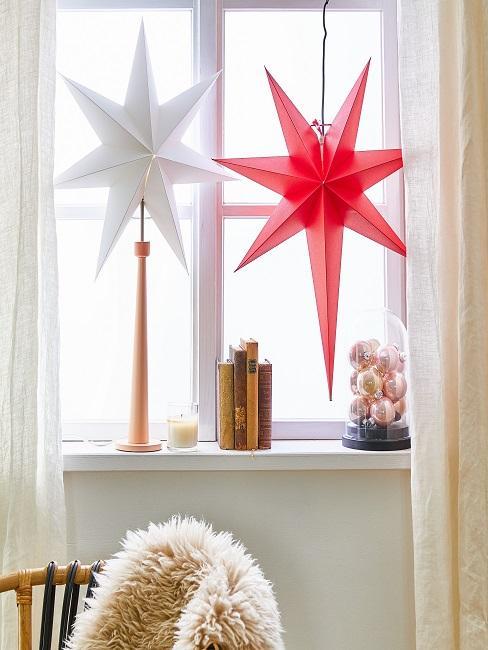 Zwei große Weihnachtssterne in einem Fenster hängend neben einer Kerze und Weihnachtskugeln