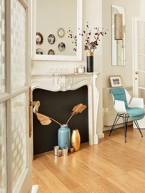 Weißes Kaminzimmer mit blauem Stuhl, blauer Vase und goldener Deko