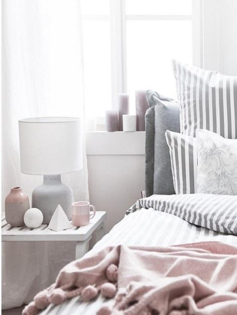 Beton Deko in Form einer Tischlampe auf dem Nachttischchen neben dem Bett.
