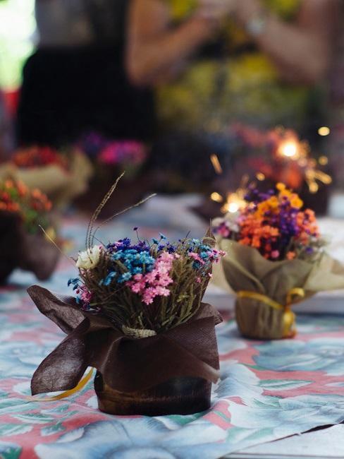 Tisch mit blumiger Tischdecke, darauf mehrere kleine bunte Blumentöpfchen
