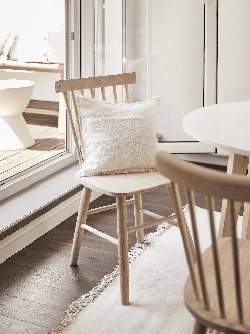 Stuhl aus hellem Massivholz mit weißem Kissen