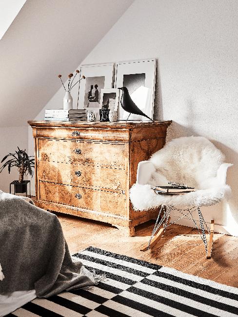 Kleines Schlafzimmer mit Kommode aus Holz, gestreiften Teppich, Sessel und Bildern