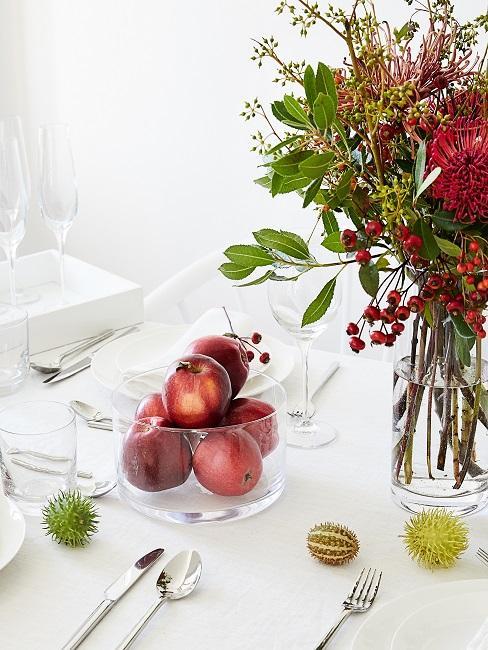 Gedeckter Tisch mit Blumen, Kastanien und einer Schüssel mit roten Äpfeln als Deko
