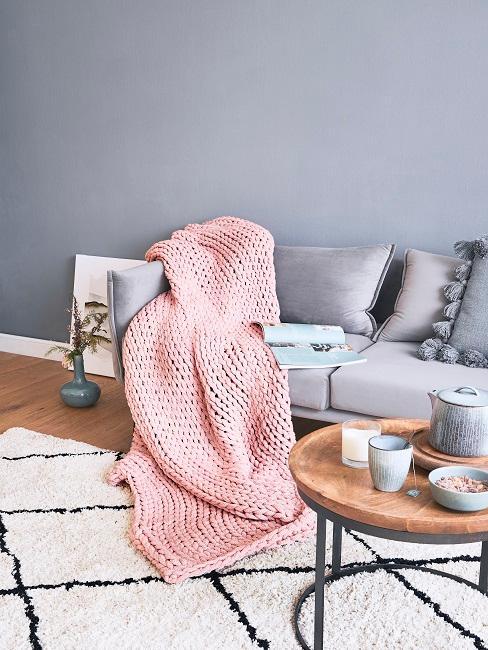 Graues Sofa hinter einem Couchtisch auf gemustertem Teppich, auf dem Sofa eine rosafarbene Chunky Knit Decke