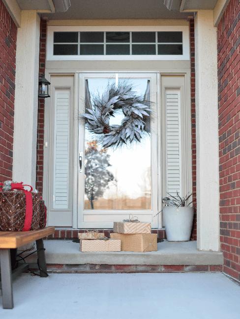 Weiße Haustür mit Kranz als Deko und Geschenken vor dem Eingang