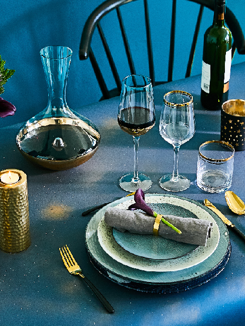 Blaue Tischdeko mit Kerzen, Vase, Gläser, Teller und Besteck