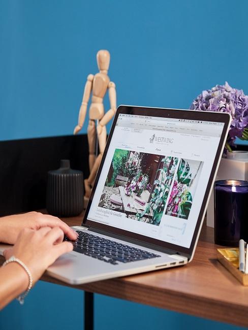 Schreibtisch mit Laptop und schöner Deko vor einer blauen Wand
