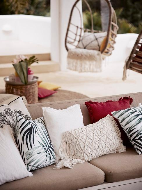 Terrasse mit einer Bank mit reichlich Kissen, im Hintergrund ein hängender Chair und ein kleiner Tisch mit Deko